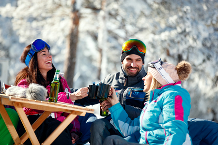 winter holidays - group of smiling friends drinking beer on break at ski resort
