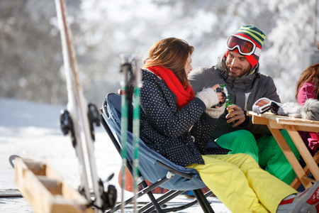 Male skier toasting with female skier in cafe on ski terrain