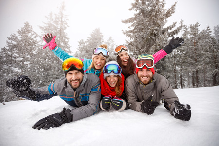 Cheerful young friends on skiing laying together on snow Stock Photo