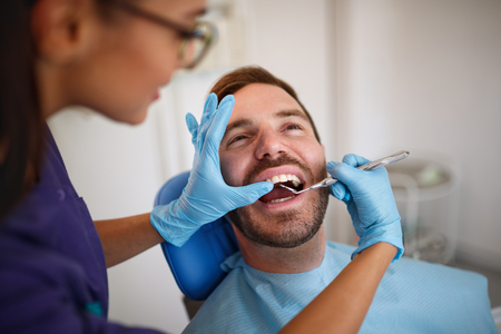 Dentist checking up patient's teeth with dental mirror in ordination