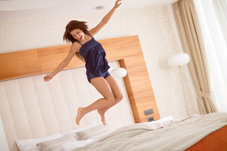 Young girl jumping on large double bed full of energy after good sleep Stock Photo - 94440521
