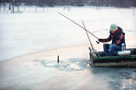 忍耐強い漁師は冬に凍った水から引っ掛けた魚を引っ張る