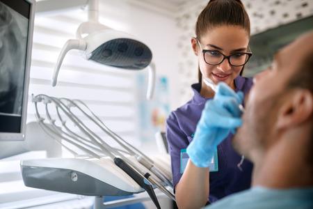 Female dentist repairing patients teeth on dental clinic