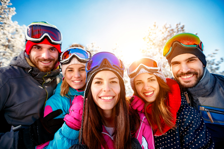portrait group of smiling friends skiers on winter holidays