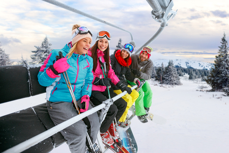 cheerful young friends on ski lift ride up on snowy mountain
