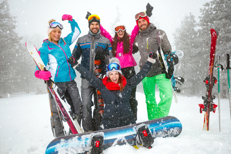 Group of smiling snowboarders having fun in the mountain