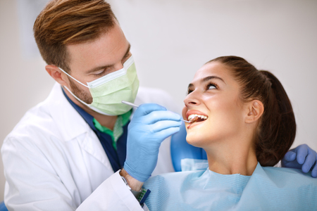 Male dentist examines girl's teeth with mirror