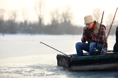 Mature fisherman fishing from boat on frost river