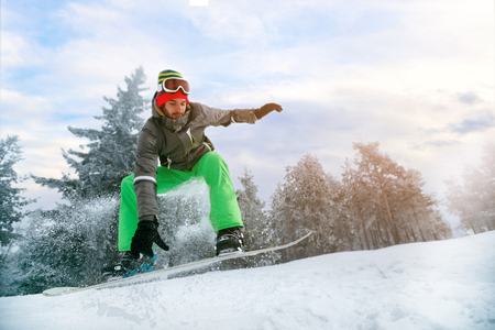 Man snowboarder in jump at ski resort in the mountain