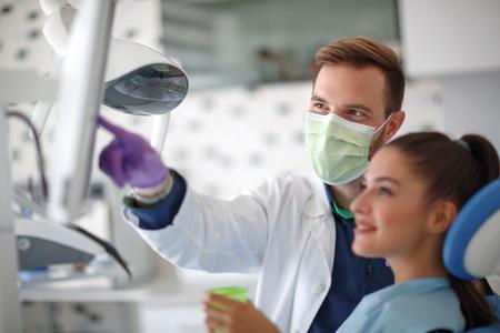 치과 진료소에서 그의 환자에게 x- 레이를 보여주는 남성 치과 의사