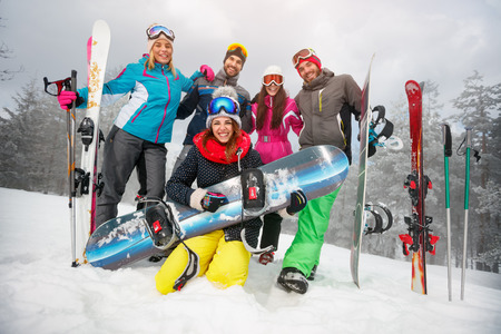 Group of happy friends having fun. Snowbarders and skiers group team friendship.