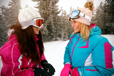 smiling girl friends skiers standing on ski slope