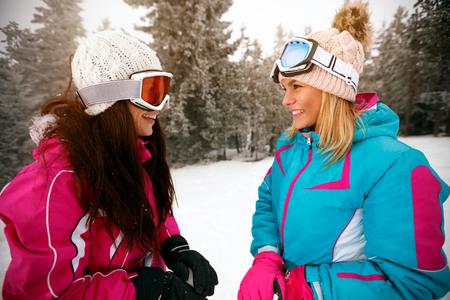 smiling girl friends skiers standing on ski slope