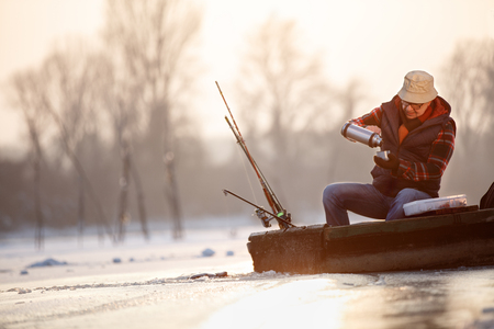Old man fishing fish on winter and taking tea in boat
