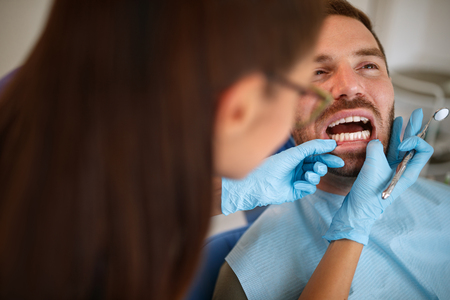 Female dentist in ambulant looking patients teeth Stock Photo