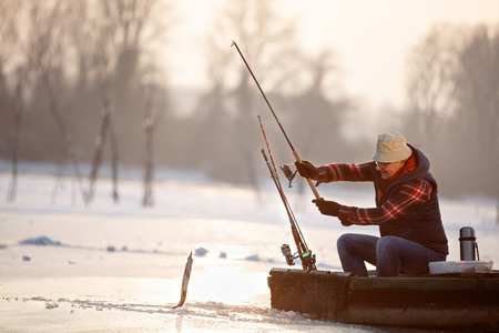 Mature fisherman draws hooked fish from water on winter Stock Photo