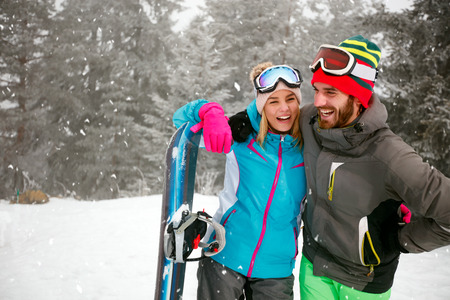 Smiling young couple spend winter holidays at snowy mountain Zdjęcie Seryjne