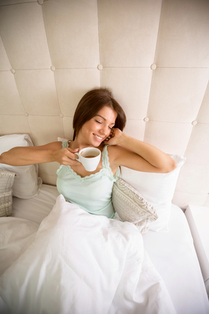 Pleasant awakening young girl with coffee in bed Stock Photo