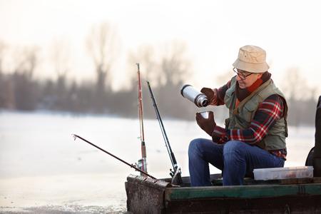 Senior fisherman taking hot tea while fishing fish on winter