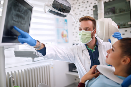 Dentist showing problem on x-ray footage with patients tooth