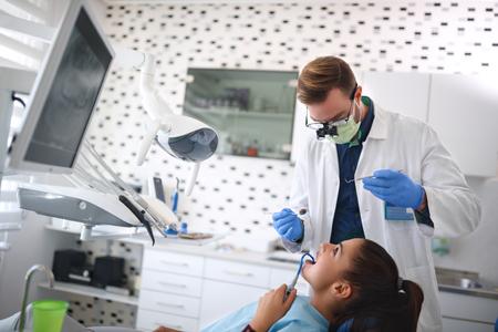 Dentist repairing female's tooth on dental clinic