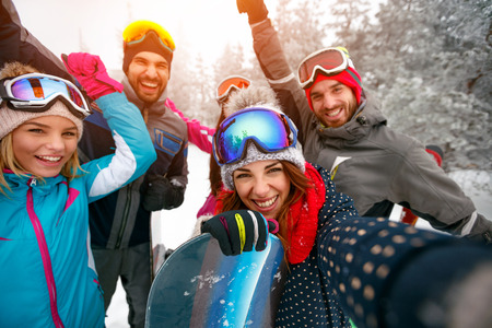 Group of smiling friends with ski on winter holidays - Skiers having fun on the snow and making selfie Zdjęcie Seryjne