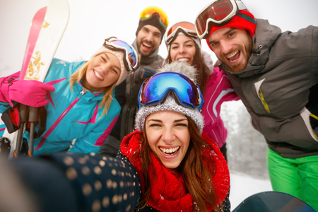 Group of smiling friends making selfie and having fun on the snow