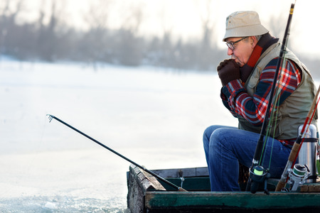 Fisherman fishing fish from boat on river on winter