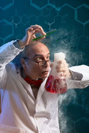 Crazy chemist scientist focused on danger experiment over abstract background