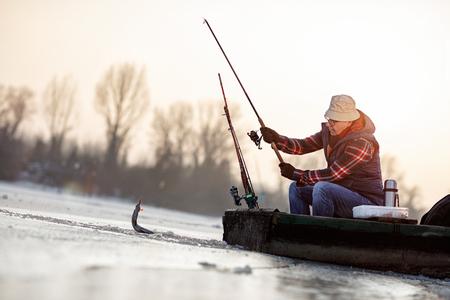 冷凍湖の上の氷釣り - シニア漁師は魚をキャッチ 写真素材