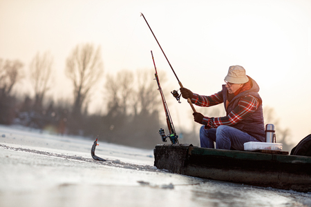 ice fishing on frozen lake- senior fisherman catch fish Archivio Fotografico