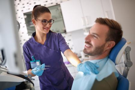 Female dentist preparing male patient for dental treatment