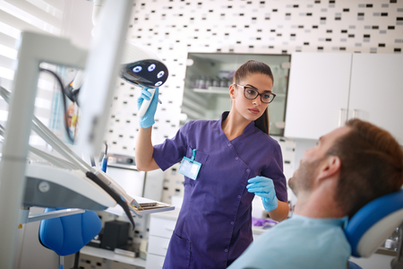 Dentist adjust reflector lamp before repairing patients teeth