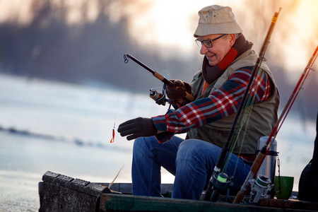 Winter hobby -elderly man fishing on lake Foto de archivo