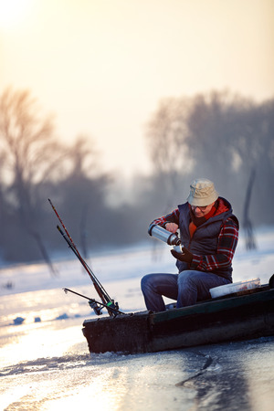 Fisherman sitting on frozen lake and drink hot tea