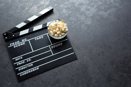 Cinema concept with movie theatre elements set of clapper board and salty popcorn