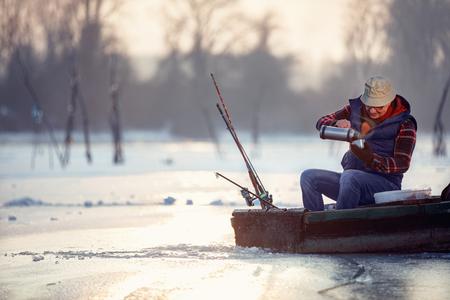 冬の季節 - 凍った湖のシニア男性と熱いお茶を飲む 写真素材