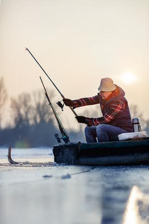 凍った湖で釣り - 幸せなシニア漁師は魚をキャッチ
