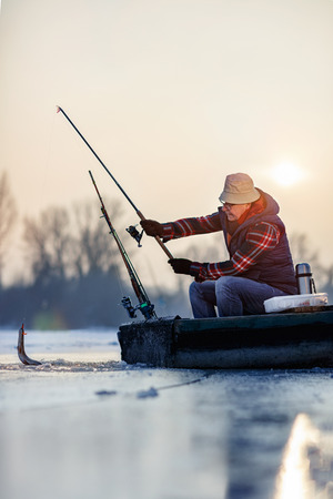 fishing on frozen lake- Happy senior fisherman catch fish Banco de Imagens