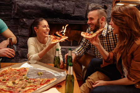 smiling friends having fun at home while toasting beer and eating pizza Standard-Bild