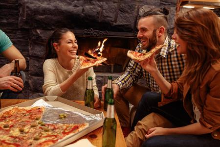 Lächelnde Freunde , die Spaß zu Hause beim Bier und essen Pizza essen