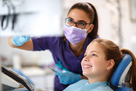 Female child in dental chair with female dentist looking at dental footage