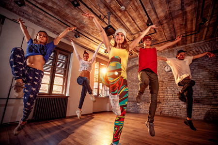 Grupa młodych tańca nowoczesnego ćwiczy taniec w skoku. Koncepcja sportu, tańca i kultury miejskiej Zdjęcie Seryjne