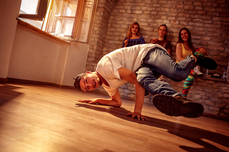 Young smiling hip hop men performs break dancing moves