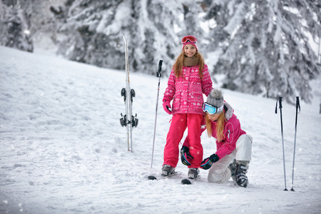 Skiing, winter, snow, sun and fun - Mother preparing for skiing happy daughter