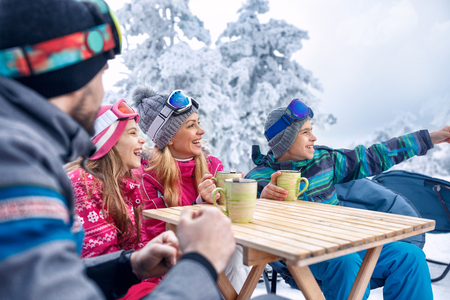 Family laughing and enjoying in hot drink at ski resort together