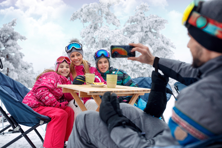 Happy family enjoying in snow and making selfie Stock Photo