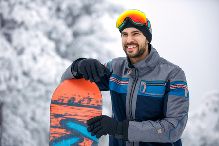 smiling snowboarder at snowy mountain Banque d'images - 104216975