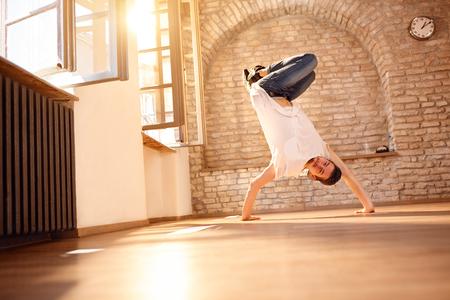 Young man break-dancer doing handstand on hands