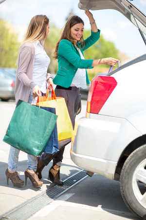 attractive young girls are put the shopping bags in the car